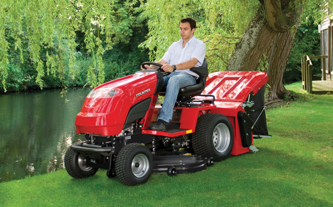 Countax A Series A25-50HE garden tractor riding mower cutting grass by tree