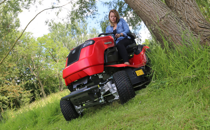 Countax B65-4WD garden tractor riding mower cutting around tree with high grass mulch deck