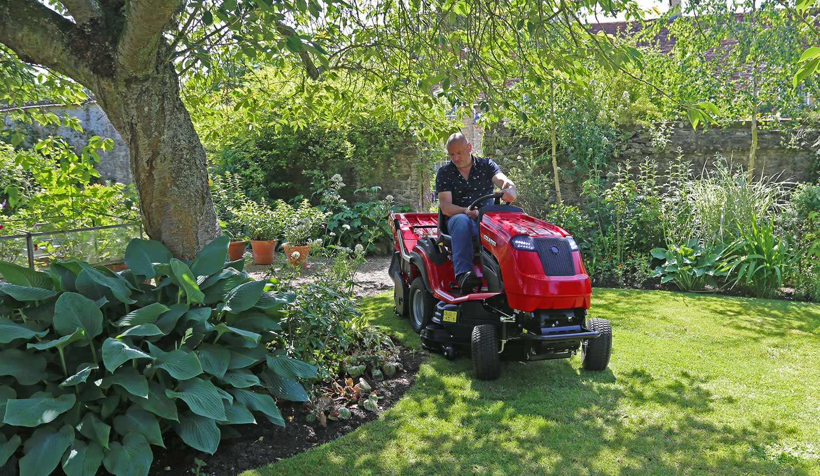 Countax C Series lawn garden tractor mower cutting grass by tree