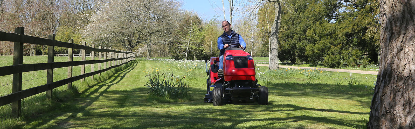 Countax C Series lawn garden tractor ride-on mower cutting and collecting grass by fence