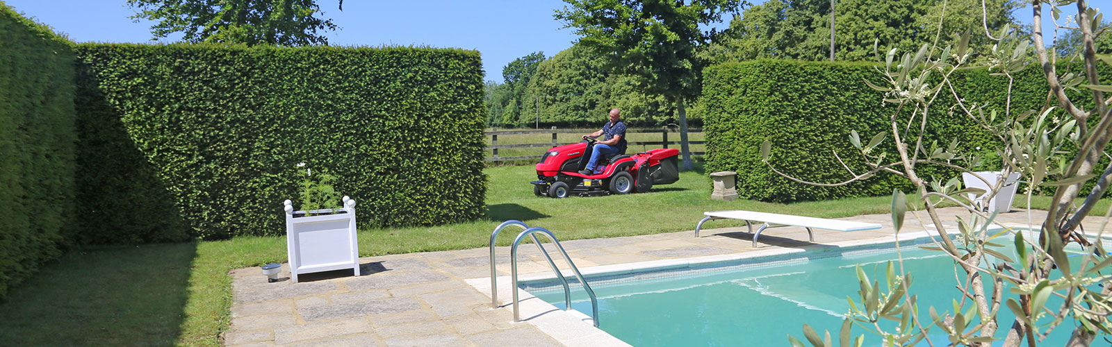 Countax C Series lawn garden tractor ride-on mower cutting and collecting grass by swimming pool
