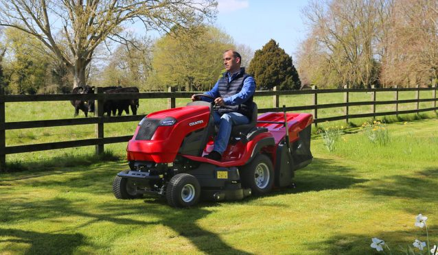 Countax C Series lawn garden tractor mower cutting grass by fence
