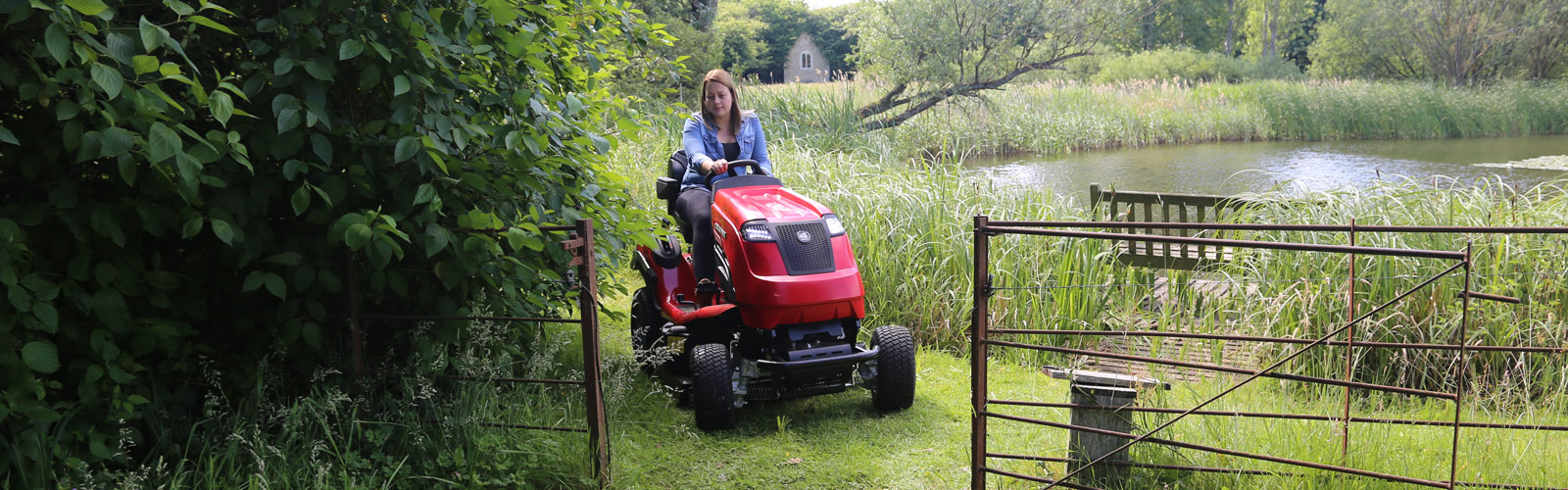 Countax B Series 4WD garden tractor riding mower with High Grass Mulch deck driving through gate by lake