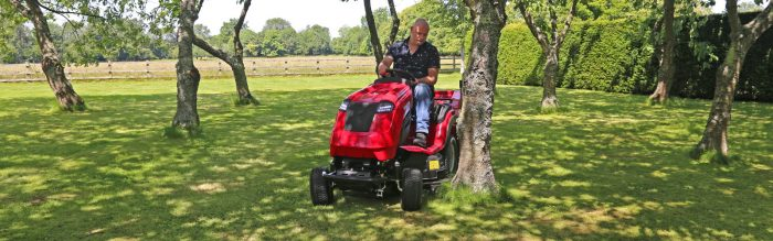 Countax C Series lawn garden tractor ride-on mower cutting around trees in orchard