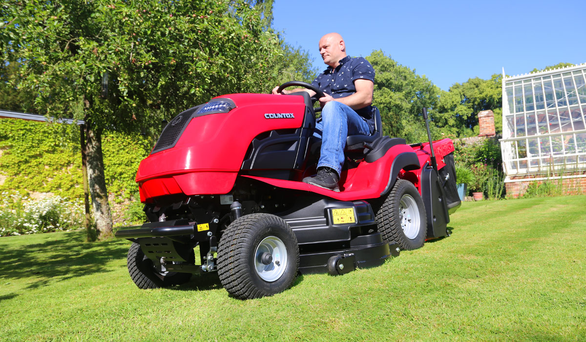 Countax C Series garden tractor with PGC+ cutting and collecting grass by greenhouse